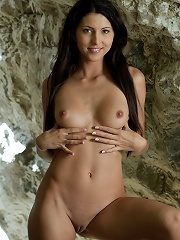 Sexy babe AnnaMaria with long black hair spread her legs and show her tits on the white rocks